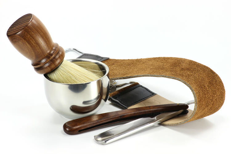 A straight razor, strop, shaving brush and bowl on a white background