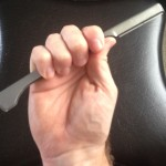 An image of a right hand holding shavette with full grip