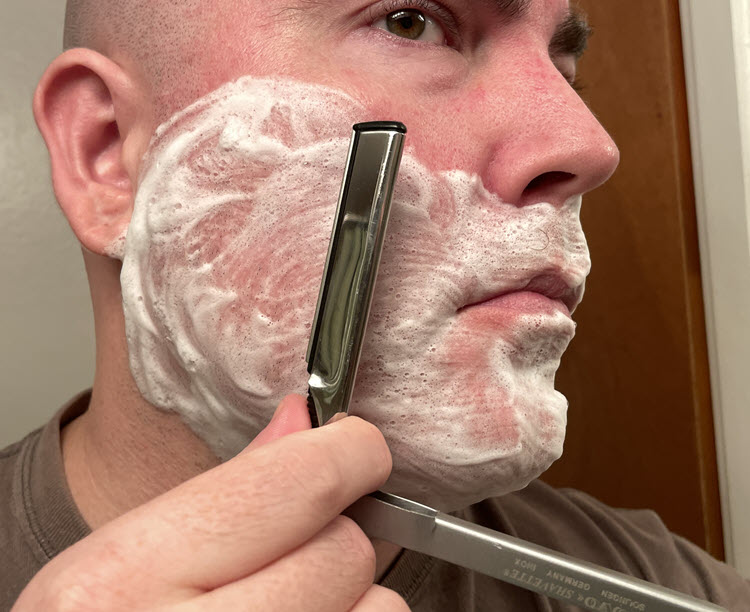 A man with a lathered face about to shave across the grain on his right cheek with a Dovo Shavette