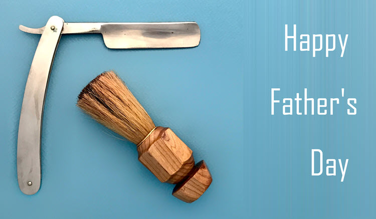 "Straight razor and shaving brush on a light blue background with the words ""Happy Father's Day"" in white."