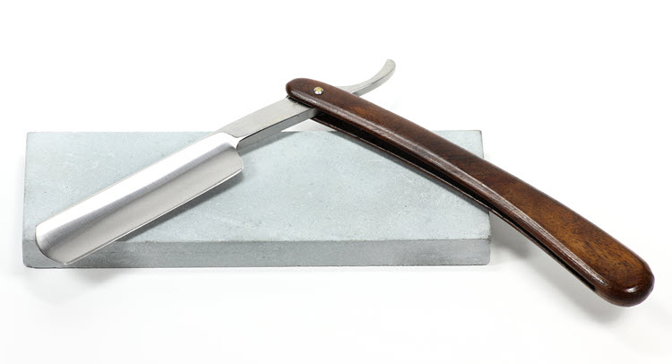 A straight razor on top of a sharpening stone