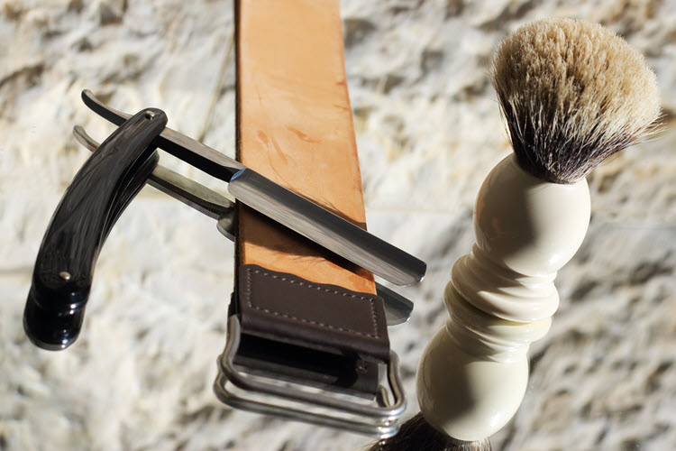 A image of a straight razor, strop, and shaving brush