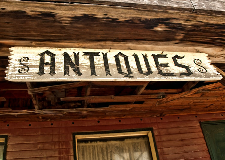 "A picture of a white sign with the word ""Antiques"" in black hanging from a red building."