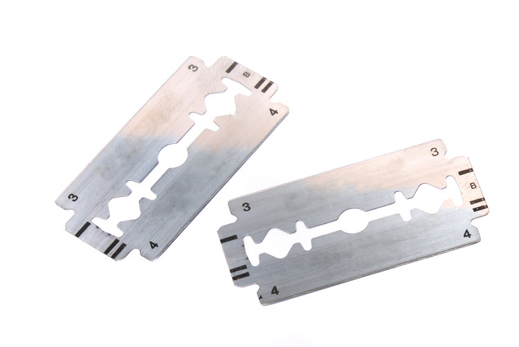 An image of two safety razor or DE blades laying against a white background