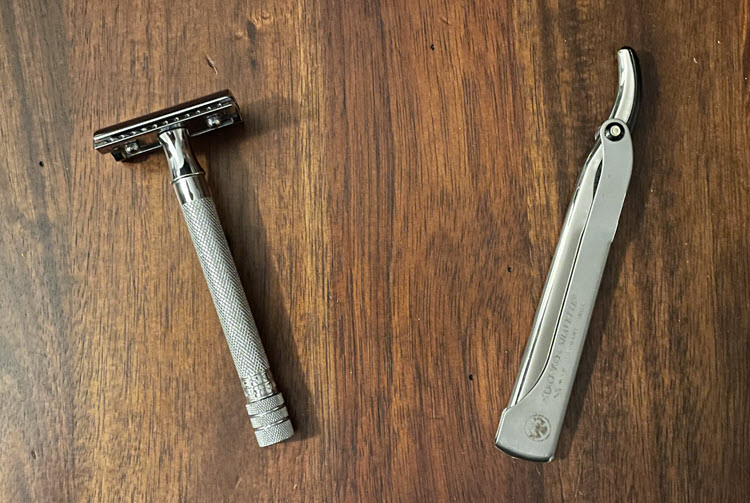 A Merkur 180 long handle safety razor and a Dovo shavette sitting on a wooden surface