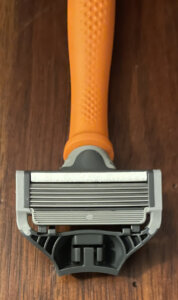 An image of a Harry's razor cartridge resting on a bright orange handle.
