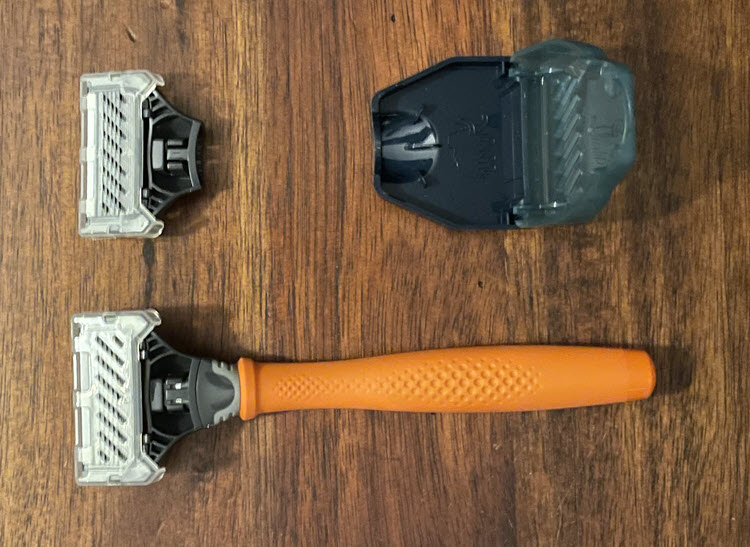 A picture showing a Harry's razor with bright orange handle, protective case and a spare cartridge razor.