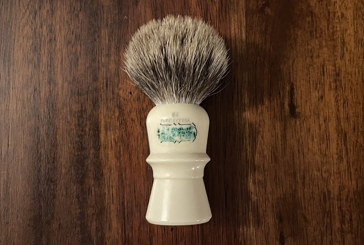 A picture of a Simpson Beaufort B4 pure badger shaving brush laying  on it's side on a wooden surface.