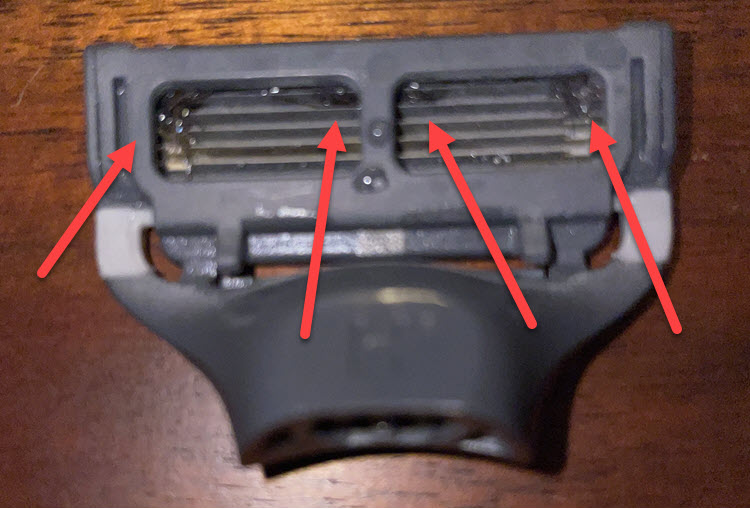 Image showing back of Harry's razor cartridge with long hair sticking out that came from my very first shave with the razor. The hair is still present even after my third shave.